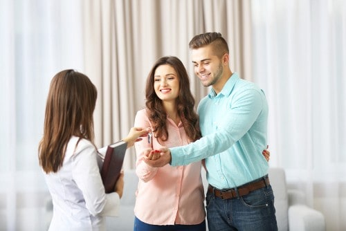 Estate-agent-giving-keys-to-couple-on-light-background
